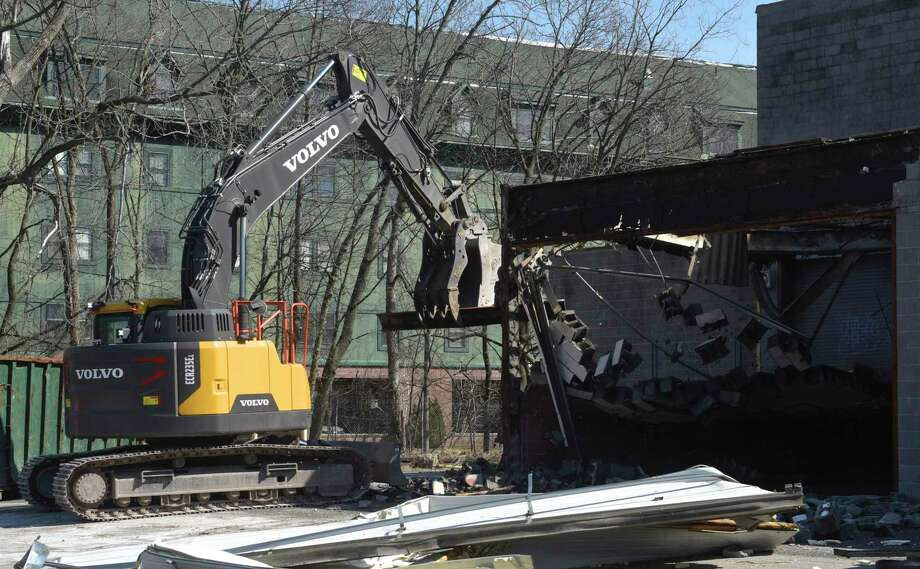 An excavator knocks down a wall during demolition work on the former News Times building at 333 Main Street in Danbury, Conn. Monday, March 2, 2020. Photo: H John Voorhees III / Hearst Connecticut Media / The News-Times