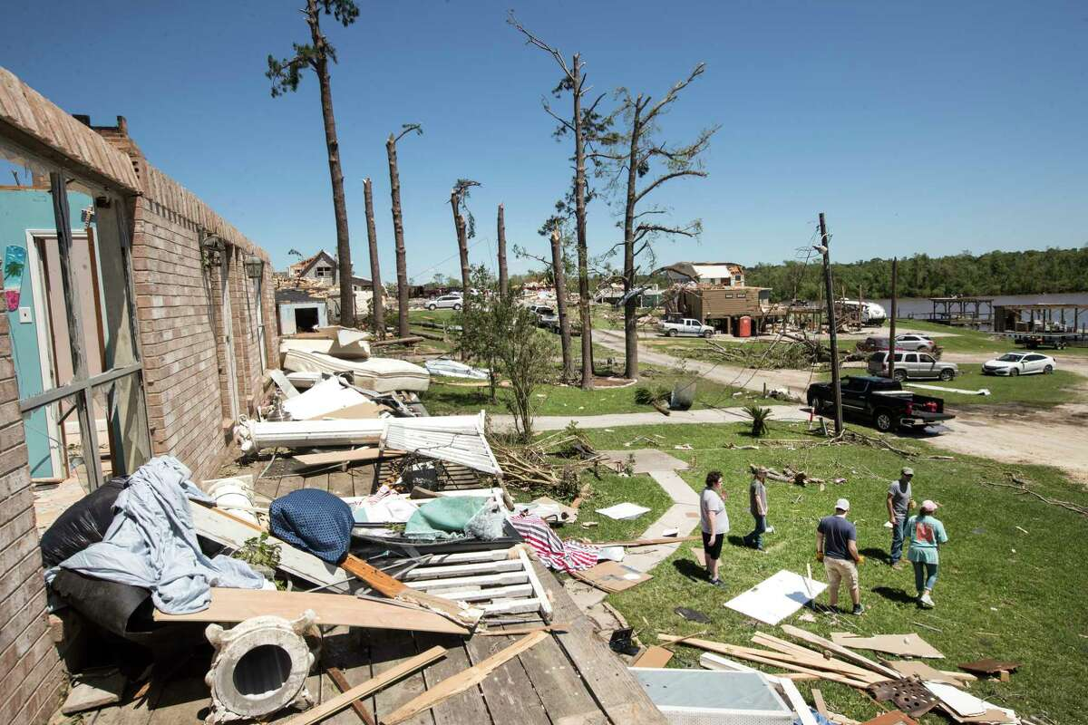 Neighbors gather on the front lawn of a heavily damaged home on Thursday, April 23, 2020, after a tornado ripped through the area in Onalaska, Texas. Several people were killed and up to 30 people were injured Wednesday as a tornado ripped through the small East Texas city, about 85 miles north of Houston.