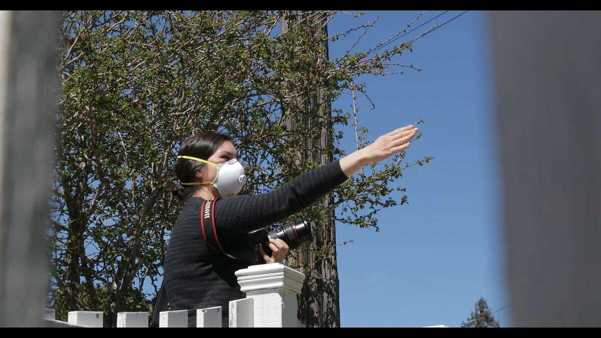 Photo journalist Jessica Christian protects herself and her subjects by wearing a mask while she directs subjects on where to stand for their portrait, during the Covid19 pandemic on April 14, 2020 in Oakland, Calif.