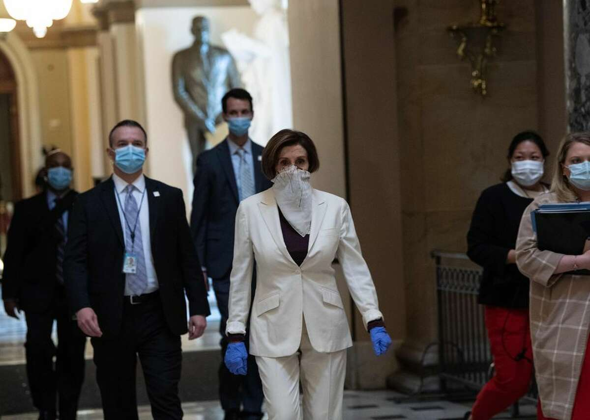 Speaker of the House Nancy Pelosi (center) walks out of the chamber of the US House of Representatives after debate April 23 on a $484 billion relief package. The bill would provide funds for the Paycheck Protection Program, along with other small-business loans, emergency relief for hospitals and money for coronavirus testing.