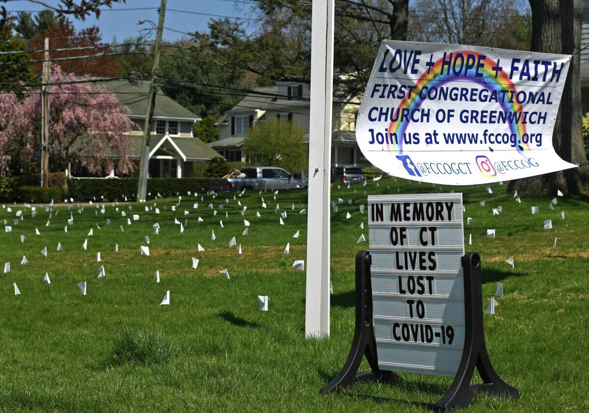 Hundreds of white flags are displayed in memory of the lives lost to COVID-19 in Connecticut at First Congregational Church of Greenwich on Sunday.