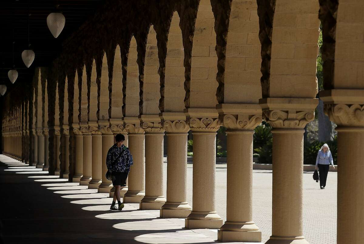 FILE - In this April 9, 2019, file photo, pedestrians walk on the campus at Stanford University in Stanford, Calif. Stanford said its April 2020 application for federal funding available in the government's multi-trillion dollar coronavirus rescue package has been withdrawn. (AP Photo/Jeff Chiu, File)