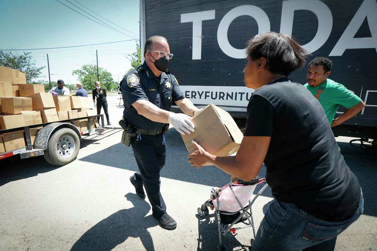 Constable Alan Rosen is thanked by a woman who received food, masks and gloves during the Constable's COVID-19 Drive-Thru Thursday, April 23, 2020, in Houston.Rosen said that they handed out over a 1,000 masks and gloves along with food to many in need. Some cars lined up as early as 6 a.m. for the give away.