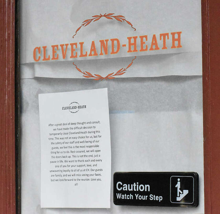 A sign hands in the entrance door of Cleveland-Heath in downtown Edwardsville announcing that it is temporarily closed during the coronavirus pandemic.