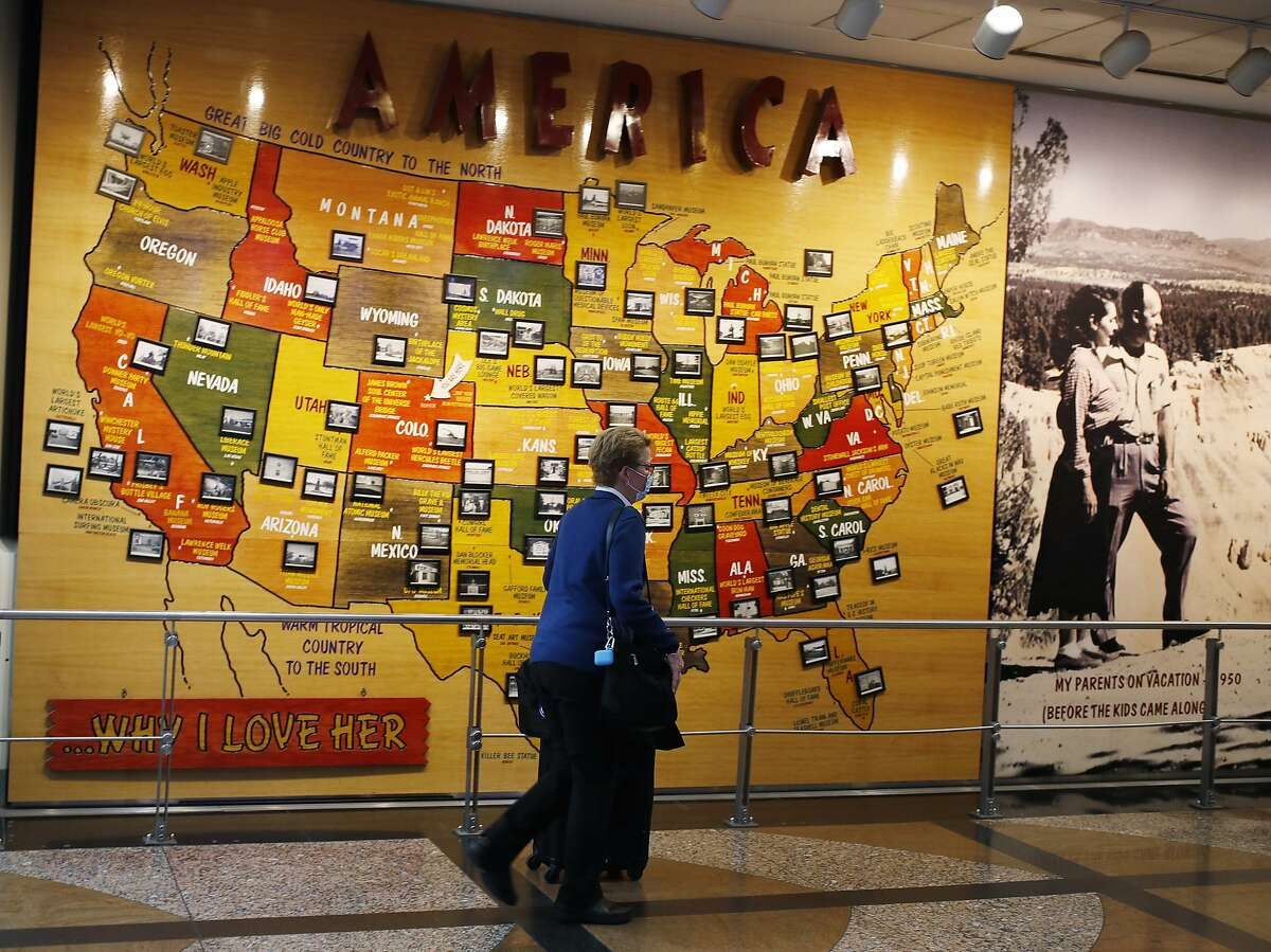 A passenger wears a face mask while pushing her luggage past a map of America in the main terminal at Denver International Airport Thursday, April 23, 2020, in Denver. (AP Photo/David Zalubowski)