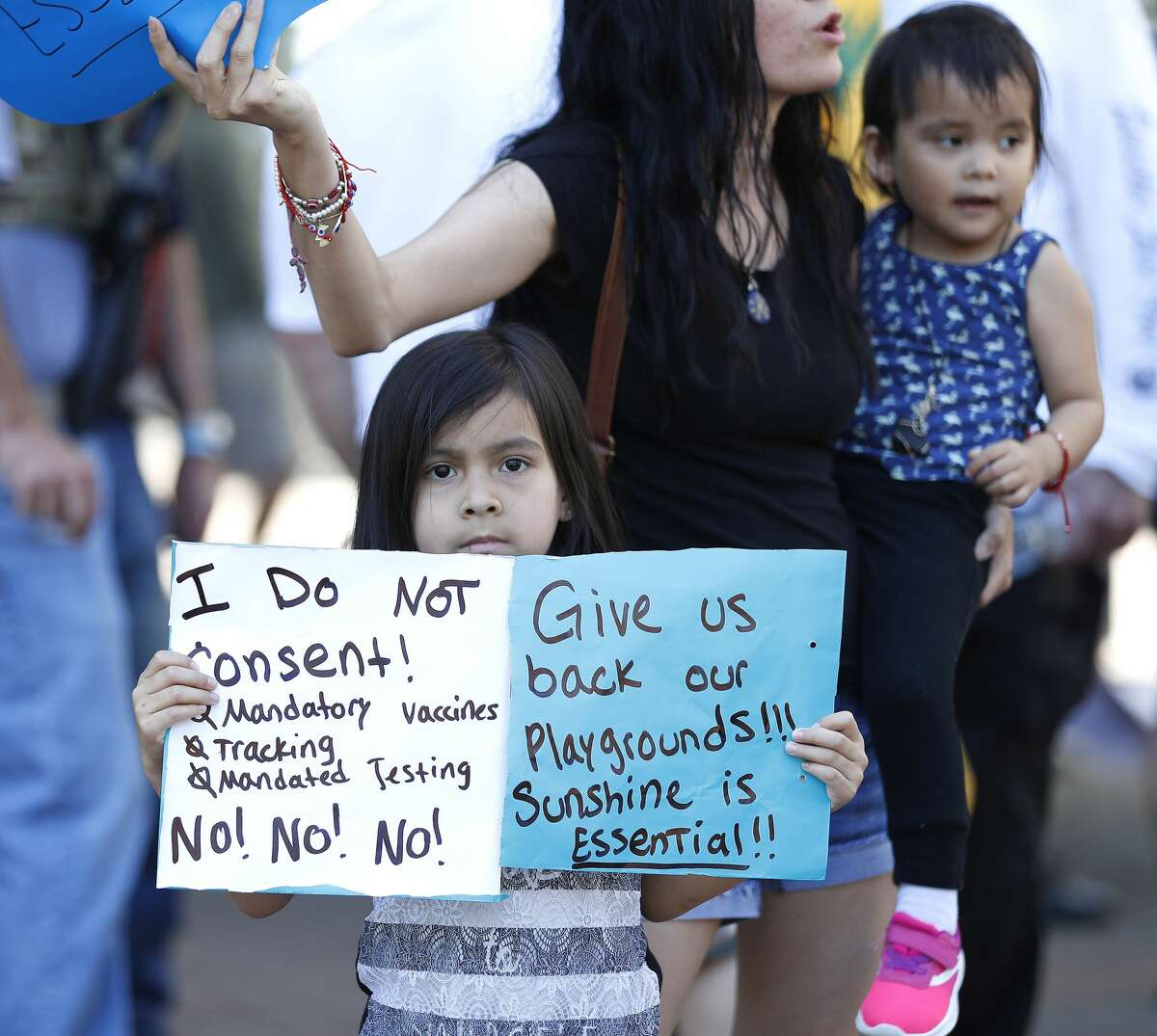 A little girl holds signs against mandatory vaccines and another saying