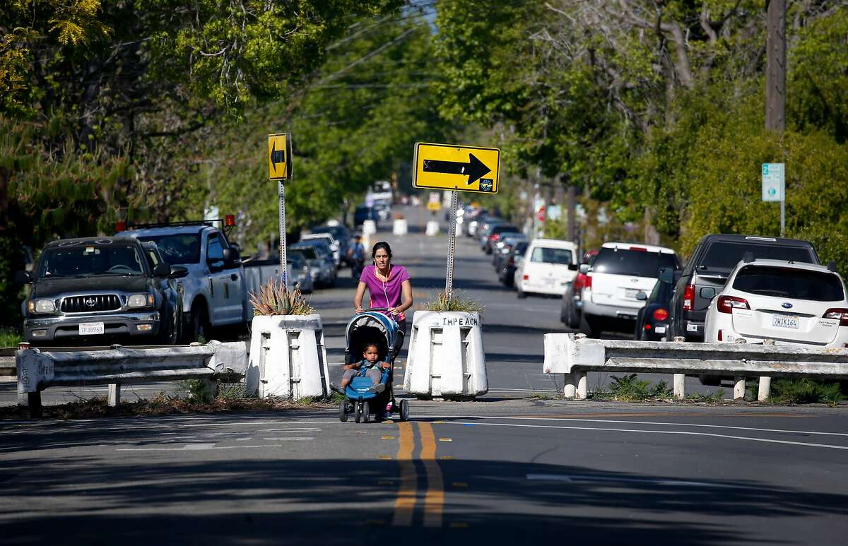 A woman pushes a stroller past barricades erected at Virginia and McGee streets to divert traffic in Berkeley, Calif. on Wednesday, April 22, 2020.