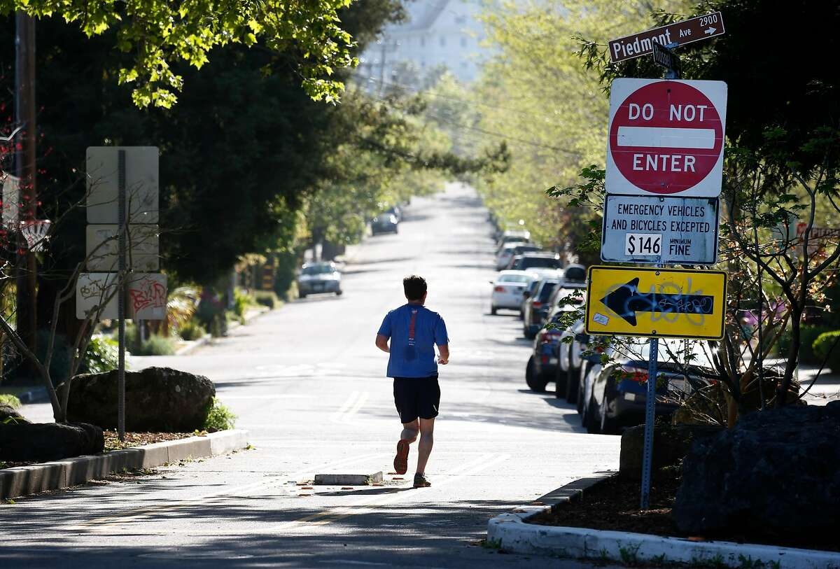 A jogger runs through a traffic diverter at Russell and Piedmont streets where only pedestrians, emergency vehicles and bicycles are allowed in Berkeley, Calif. on Wednesday, April 22, 2020.