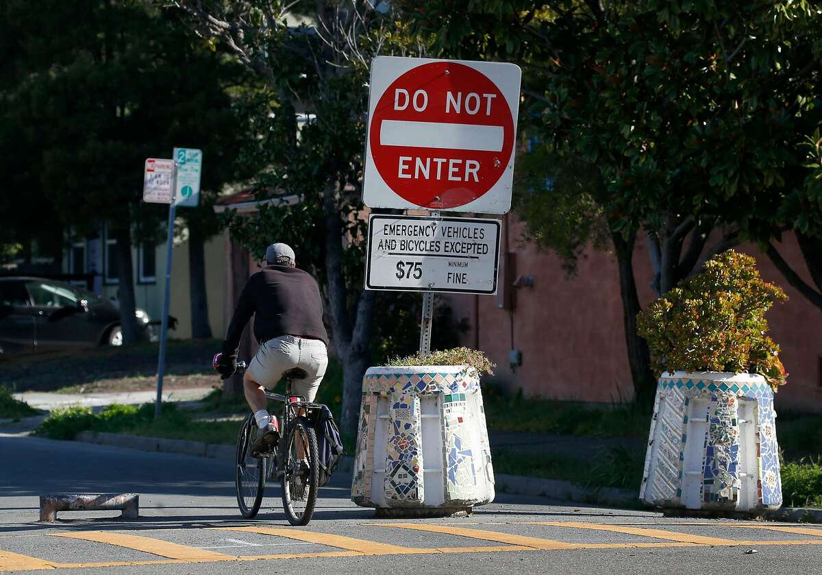 A bicyclist rides past barricades that prevent traffic from entering northbound Fulton Street from Ashby Avenue in Berkeley, Calif. on Wednesday, April 22, 2020.