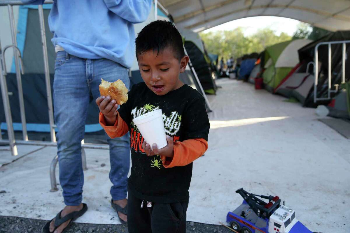 Standing by his father, four-year-old Yarbin Isaac Alvarado Mendoza of Honduras, eats sweet bread with coffee at a migrant camp in Matamoros, Mexico, Thursday, Feb. 6, 2020. The boy and his dad have been at the camp for the past three months. Their second hearing before a U.S. immigration judge is scheduled for May 22.