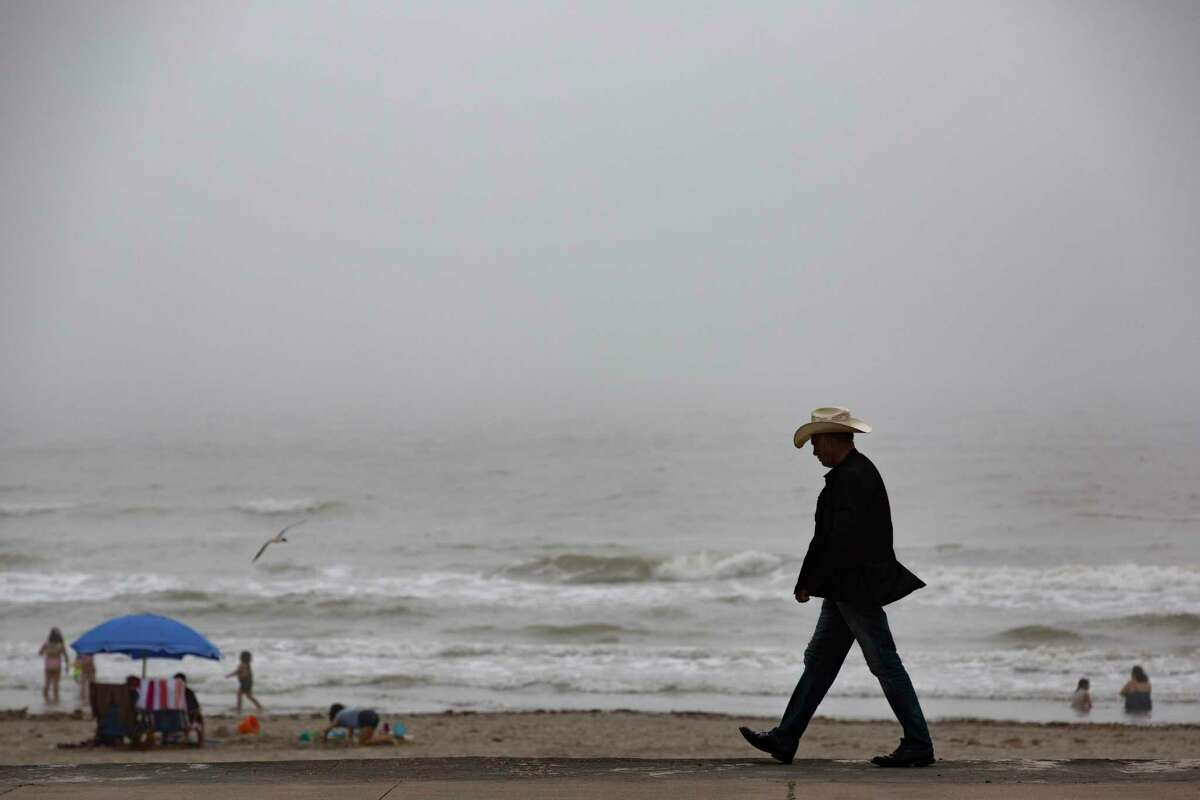 A man walks by the beach in Galveston on Sunday, March 15, 2020.