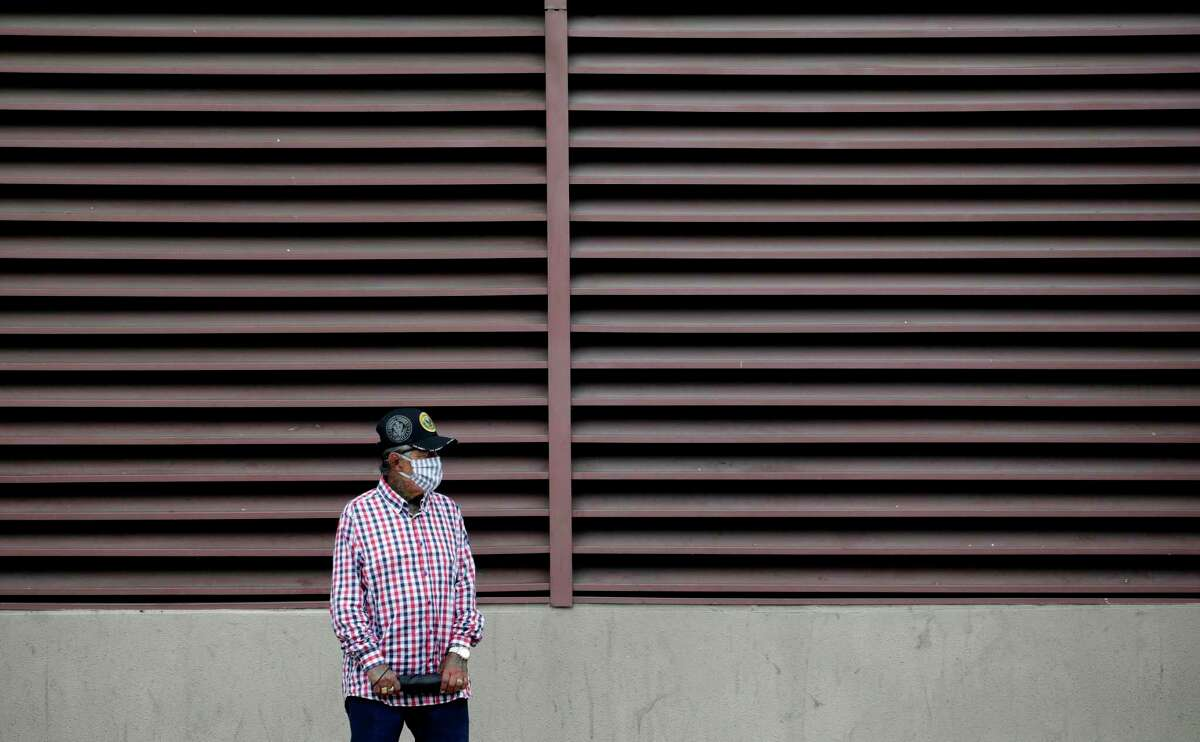 A man wears a face mask as he waits for a bus in San Antonio on Wednesday. VIA Metropolitan Transit has gone to a