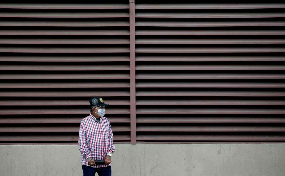 """A man wears a face mask as he waits for a bus in San Antonio on Wednesday. VIA Metropolitan Transit has gone to a """"Sunday"""" schedule on more than half of its routes, and eliminated five more altogether. (AP Photo/Eric Gay) Photo: Eric Gay /Associated Press / Copyright 2020 The Associated Press. All rights reserved."""