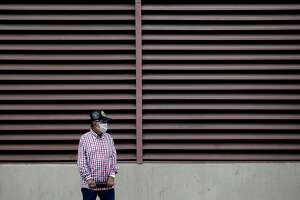"A man wears a face mask as he waits for a bus in San Antonio on Wednesday. VIA Metropolitan Transit has gone to a ""Sunday"" schedule on more than half of its routes, and eliminated five more altogether. (AP Photo/Eric Gay)"