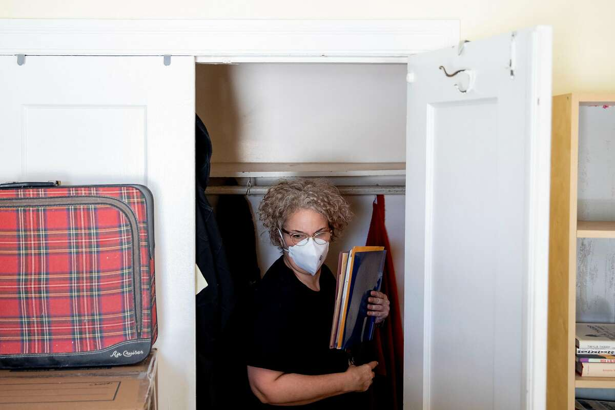 Kristin Demoro gathers family relics from her closet while packing up belonging at her apartment in Oakland.
