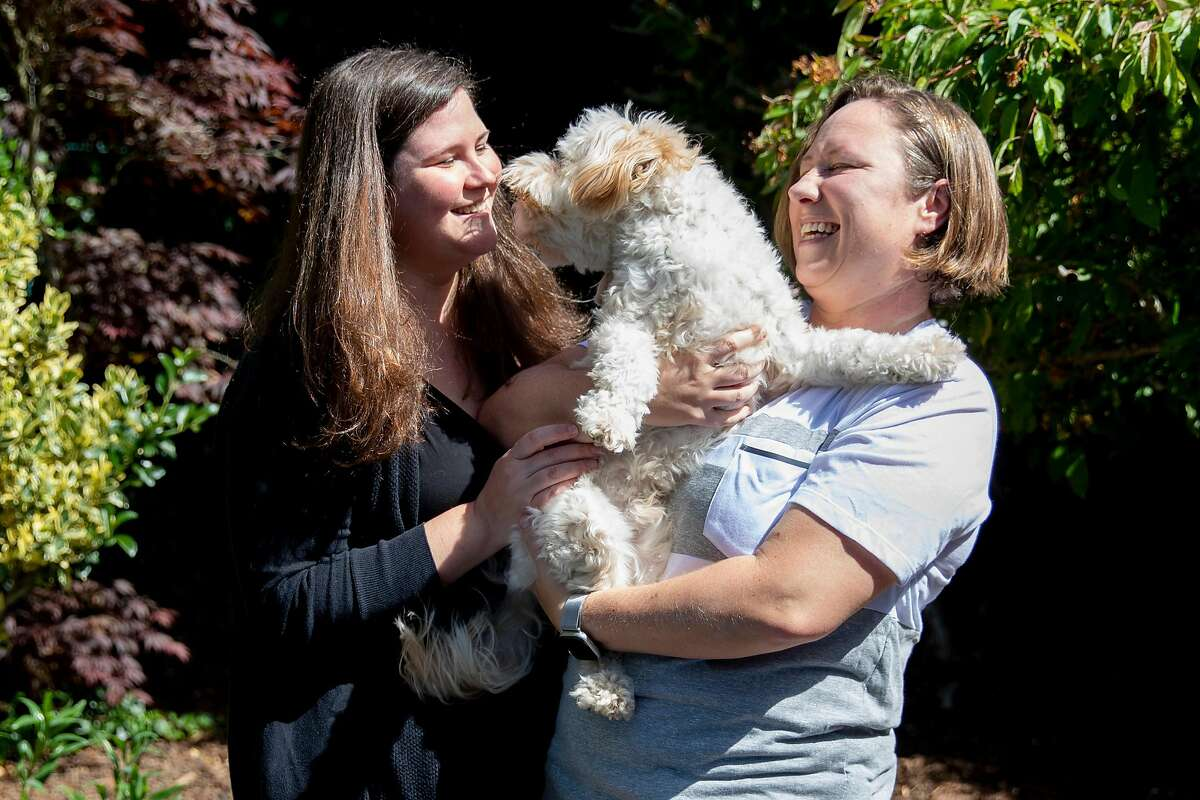 (From left) Jamie and Tarah Burns play with their dog Finnegan in the backyard of their home in San Francisco, Calif. Thursday, April 23, 2020. After years of waiting, they were scheduled to undergo fertility treatments to get pregnant this spring. But the coronavirus pandemic closed fertility clinics and has delayed their treatment indefinitely. They've gone from expecting to be pregnant in 6 weeks to not knowing when they'll be able to build their family.