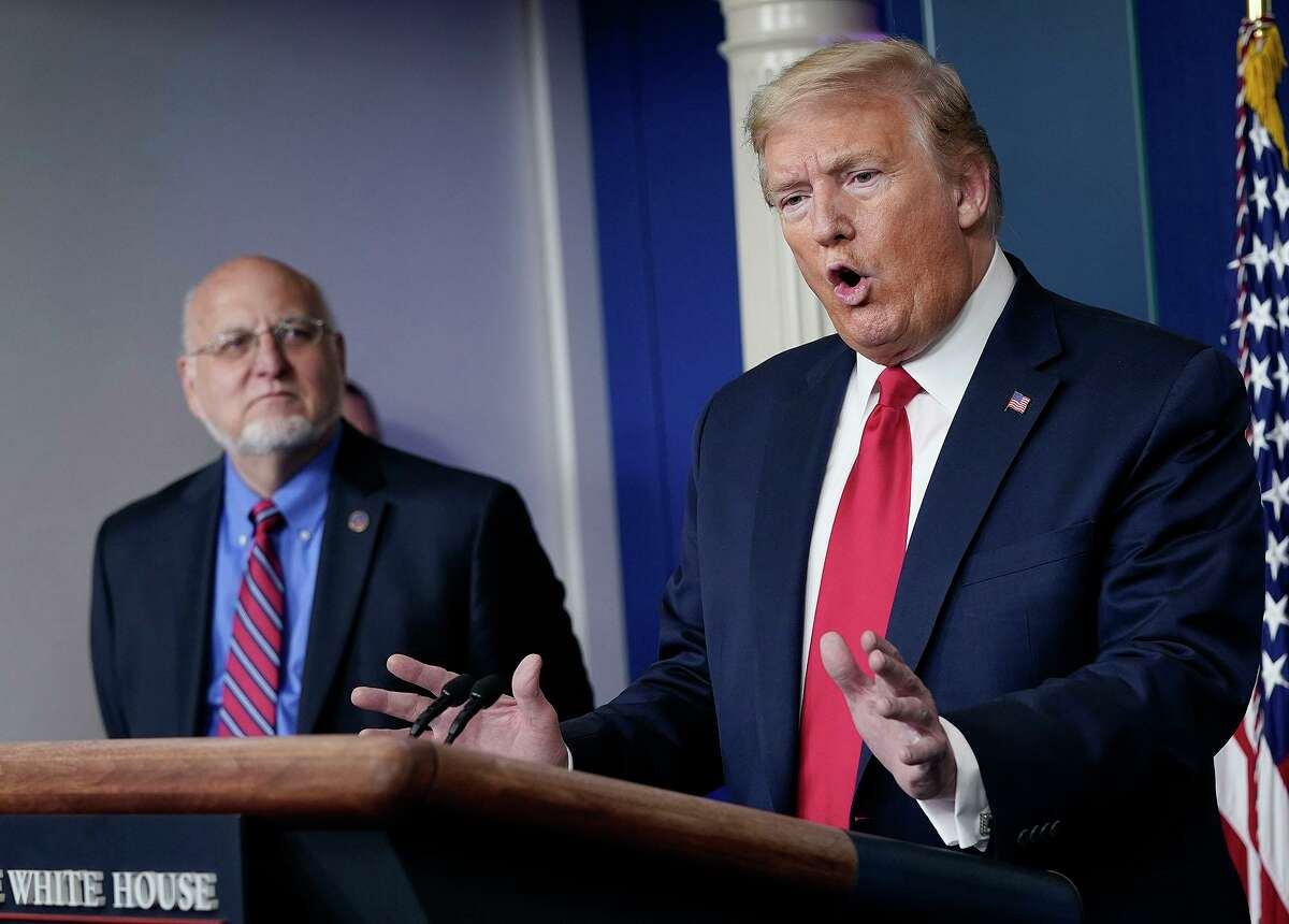 President Donald Trump, right, speaks while Dr. Robert Redfield, Director of the Centers for Disease Control and Prevention, looks on during the daily briefing of the coronavirus task force at the White House in Washington, D.C., on Wednesday, April 22, 2020. (Drew Angerer/Getty Images/TNS)