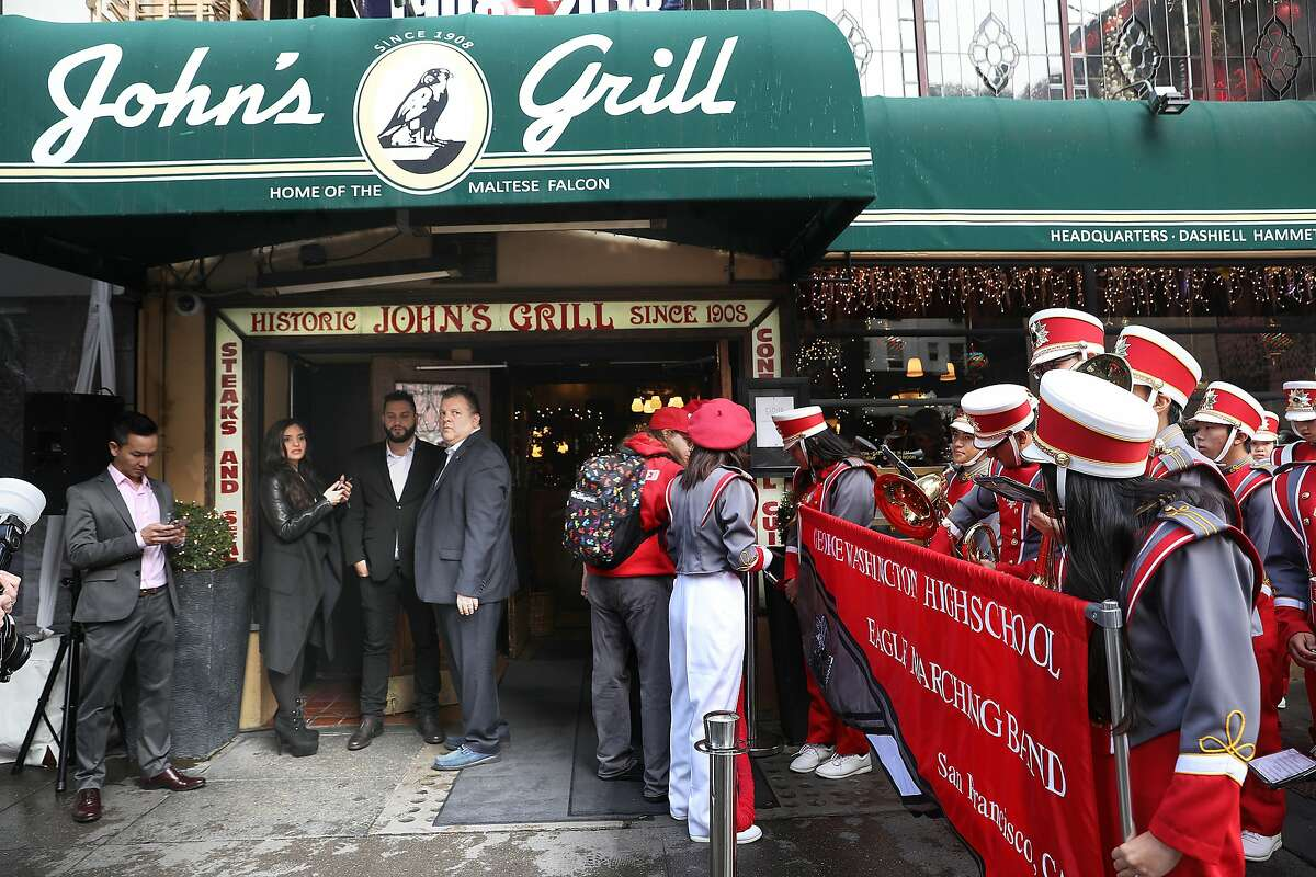 John's Grill celebrates its 110th anniversary with owner John Konstin (rmiddle) and his daughter Sydna Constin (left) and son John Konstin (between them) as well as the George Washington High School marching band (far right) as they wait to greet guests on Thursday, Nov. 29, 2018, in San Francisco, Calif.