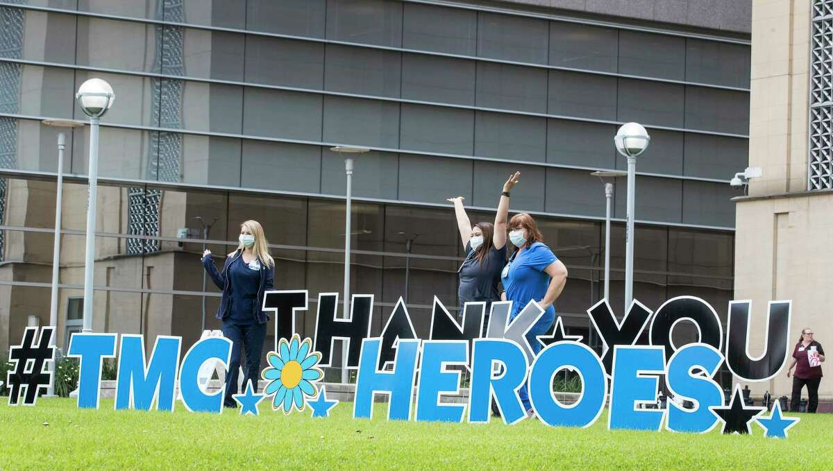 """A trio of workers in the Texas Medical Center pose for a photo by a sign thanking the """"TMC Heroes"""" working to fight the coronavirus pandemic on Tuesday, April 7, 2020 in Houston."""