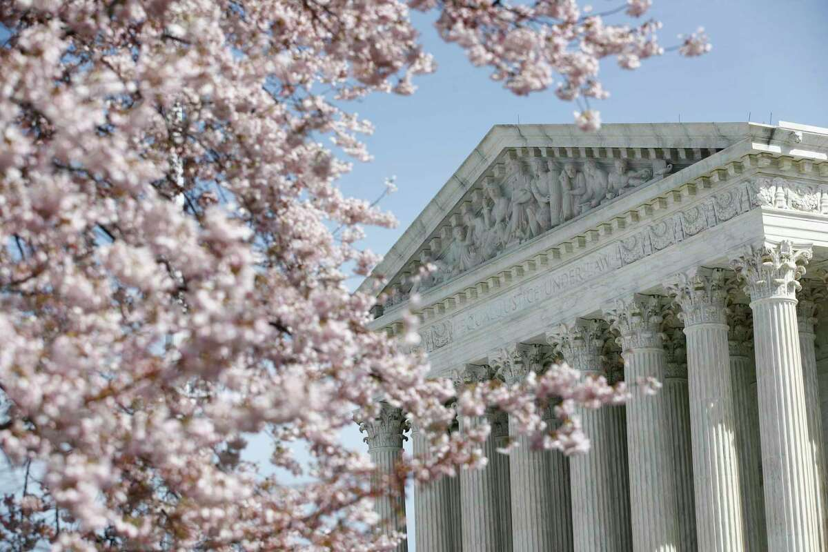FILE - In this March 16, 2020, file photo, a tree blooms outside the Supreme Court in Washington. The Supreme Court ruled Thursday, April 23, that sewage plants and other industries cannot avoid environmental requirements under landmark clean-water protections when they send dirty water on an indirect route to rivers, oceans and other navigable waterways. (AP Photo/Patrick Semansky, File)