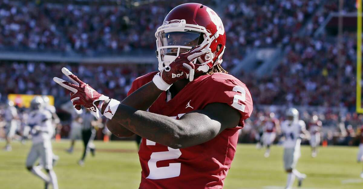 In this Oct. 27, 2018, file photo, Oklahoma wide receiver CeeDee Lamb (2) celebrates a touchdown during an NCAA college football game against Kansas State in Norman, Okla. (AP Photo/Sue Ogrocki, File)