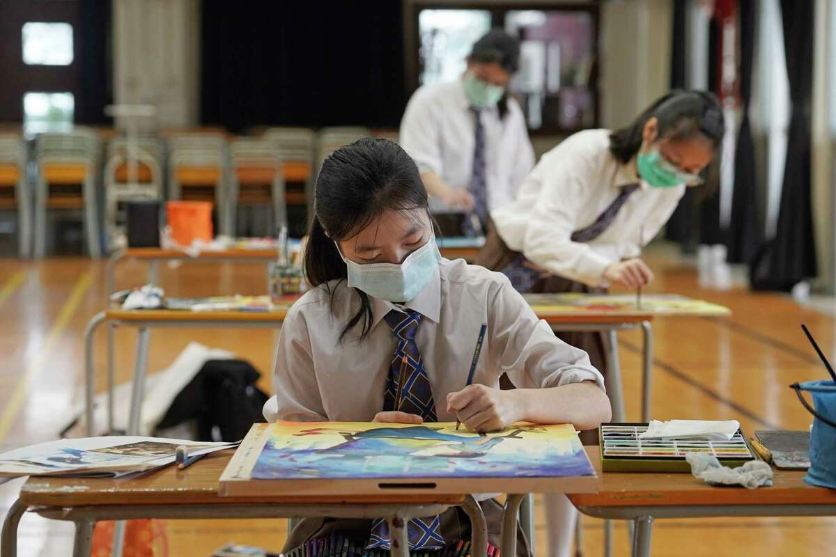 In this Monday, March 9, 2020, photo, students wearing masks to help stop the spread of the new coronavirus, participate in the visual arts mock exam for Diploma of Secondary Education (DSE) at the CCC Ming Kei College in Hong Kong. Hong Kong's university entrance examinations have started with social-distancing measures. More than 52,000 students are expected to sit for the city's Diploma of Secondary Education exams over the next month.