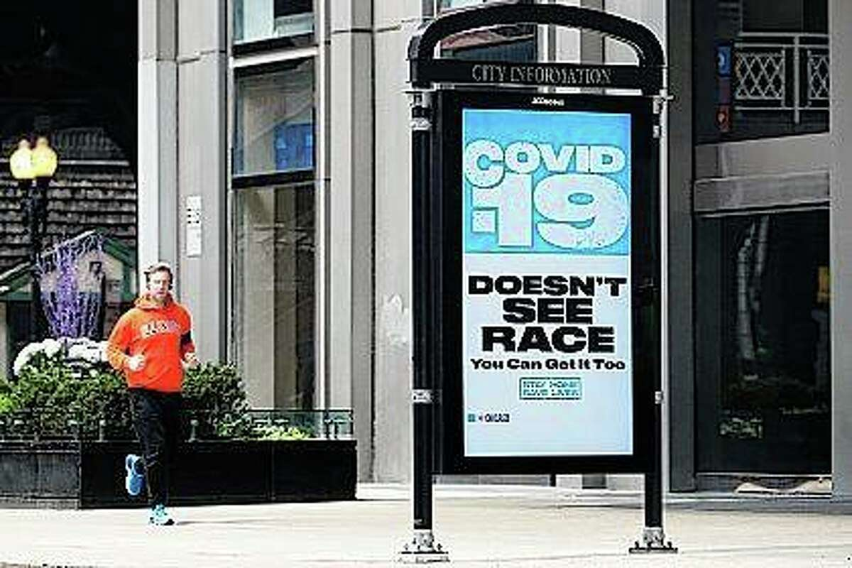 A lone jogger approaches a sign Wednesday in downtown Chicago advising people to stay home to help fight the COVID-19 pandemic. Illinois Gov. J.B. Pritzker has extended the statewide stay-at-home order through May.