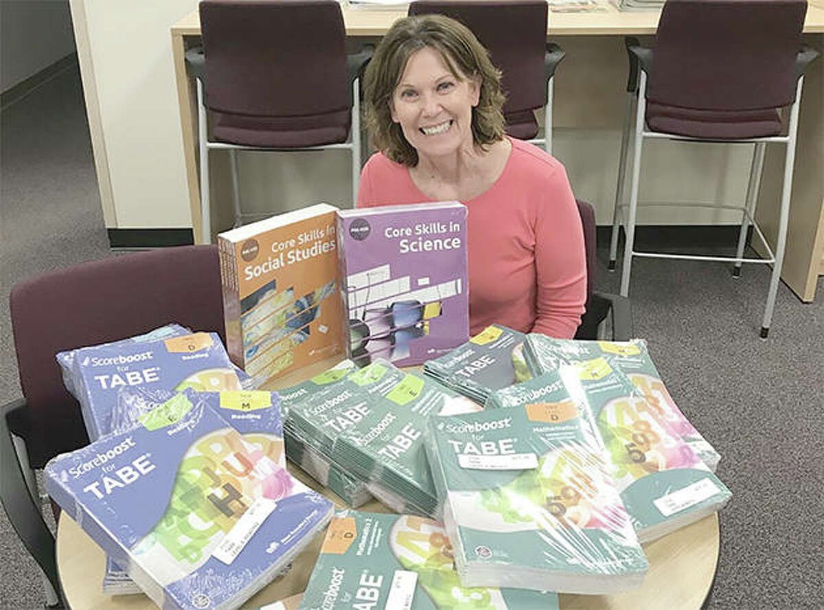 Monica Foster, manager of adult education at John Wood Community College, unpacks bundles of books. The materials were supplied through a grant sponsored by the Rotary Club of Pike County to provide students with study materials as they continue their GED preparations at home.