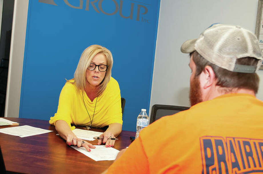 Amy Hageman, a broker at the Real Estate Group in Jacksonville, practices social distancing during the COVID-19 pandemic as she writes up an offer Wednesday afternoon at her office. Photo: Darren Iozia   Journal-Courier