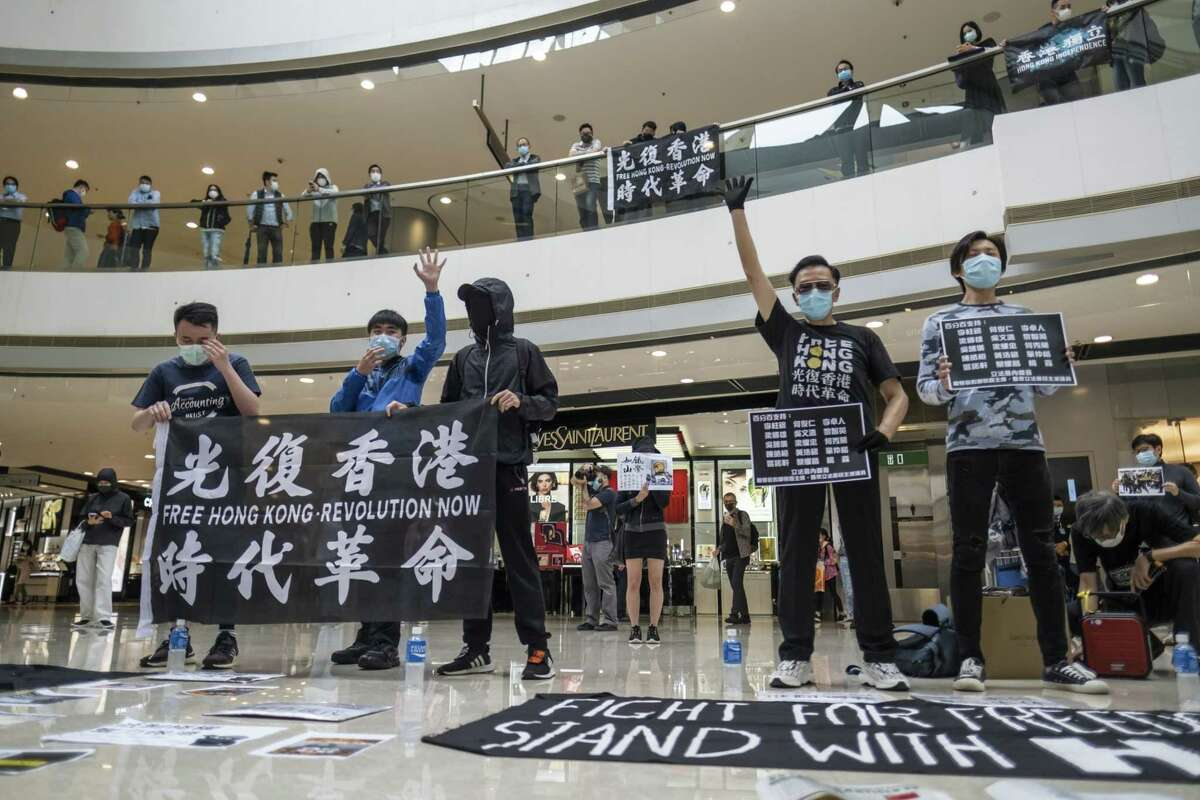 Demonstrators wearing protective masks hold placards and banners while standing spaced apart during a protest in the atrium of the International Finance Center Mall in Hong Kong on April 24, 2020.
