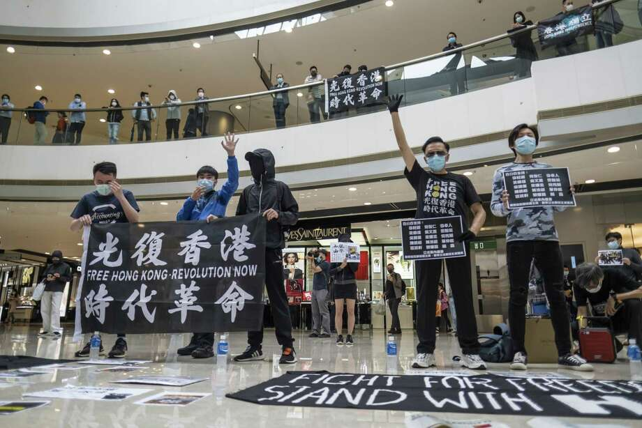 Demonstrators wearing protective masks hold placards and banners while standing spaced apart during a protest in the atrium of the International Finance Center Mall in Hong Kong on April 24, 2020. Photo: Bloomberg Photo By Justin Chin. / © 2020 Bloomberg Finance LP