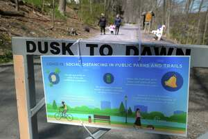 Signs are in place along the Pequonnock River Trail to remind visitors to maintain proper social distancing during the COVID-19 crisis, seen here in Trumbull, Conn. April 16, 2020.