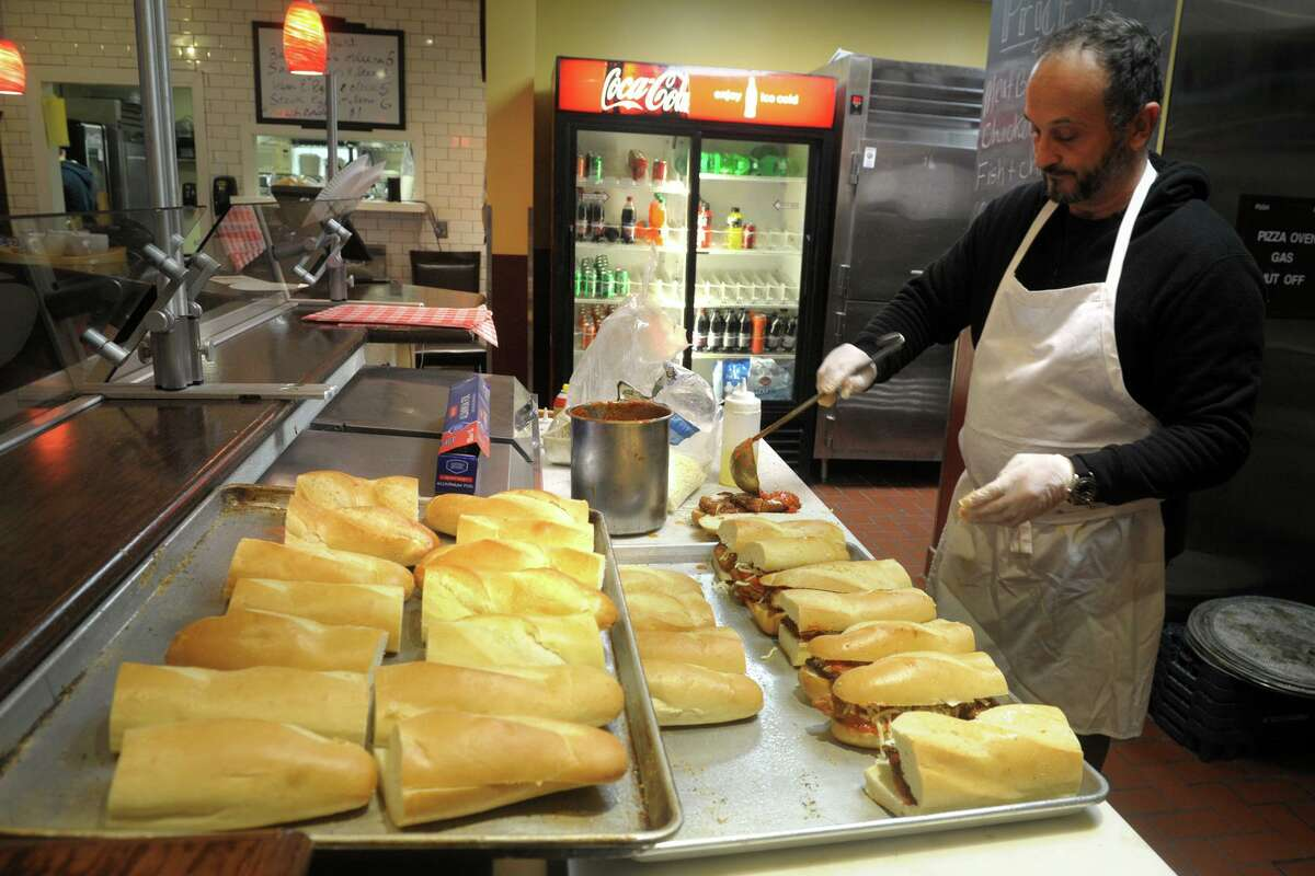 Claudio Sanfrancesco prepares chicken parmesan sandwiches in the kitchen at The Levee, a sports bar on the campus of Fairfield University, in Fairfield, Conn. April 21, 2020. While the campus has been closed, Sanfranceso has been making hot meals and delivering them to area hospitals twice a week.
