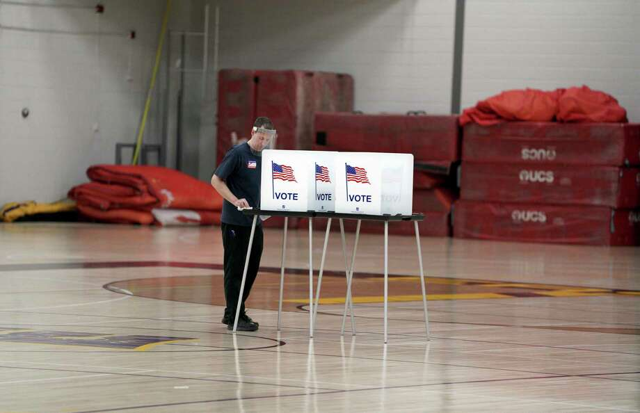 A worker disinfects voting booths after being used as voters, ignoring a stay-at-home order over the coronavirus threat, cast ballots in the state's presidential primary election in the gym at East High School on April 7 in Madison, Wis. Photo: Associated Press / WISCONSIN STATE JOURNAL