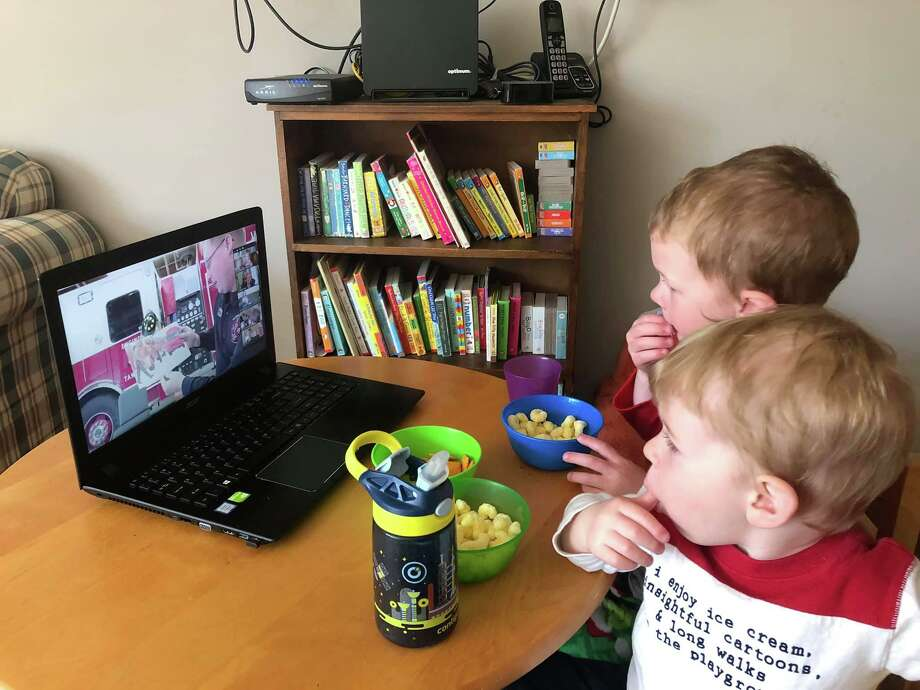 Nathaniel and Charles Dey of Wilton watch Firefighter Story Time from their home. In conjunction with Wilton Library, each Friday from 10 to 10:30 a.m., Wilton firefighters read stories to children on Zoom. Registration for this program is required at wiltonlibrary.org/events. For questions, email aszabo@wiltonlibrary.org. Photo: Lynn Dey / Wilton Bulletin Contributed