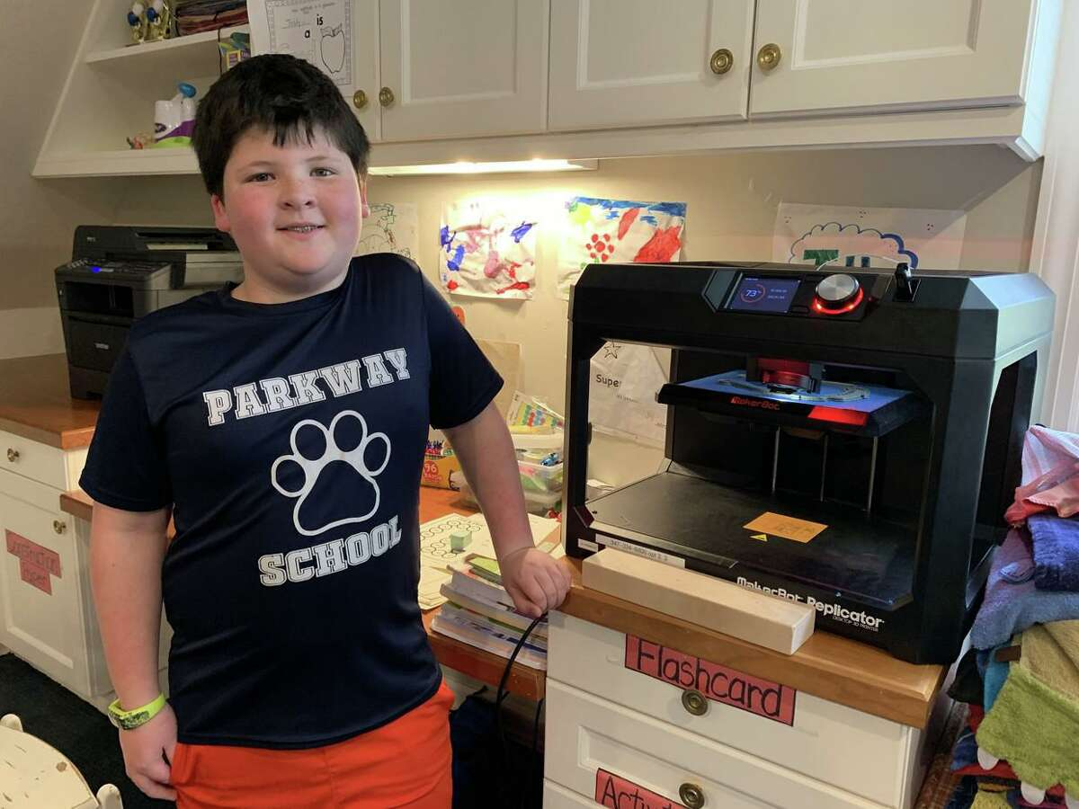 Parkway School fourth grader Teddy Curreri poses next to his 3D printer, which he used to print shields for hospital workers at Stamford Hospital. PTA Vice President Meredith Curreri and his mother supplied the plastic through her employer, Synchrony, and its #GearUp program.
