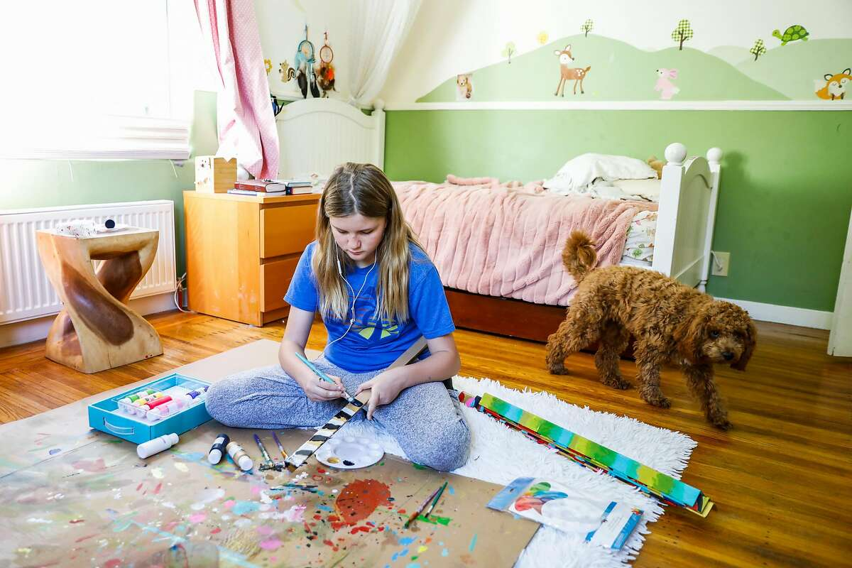 Rory Schroeder,11, listens to �39 Clues� on her phone while working on an art project as her dog Juneau looks on at her home during shelter-in-place orders on Thursday, April 23, 2020 in Berkeley, California.