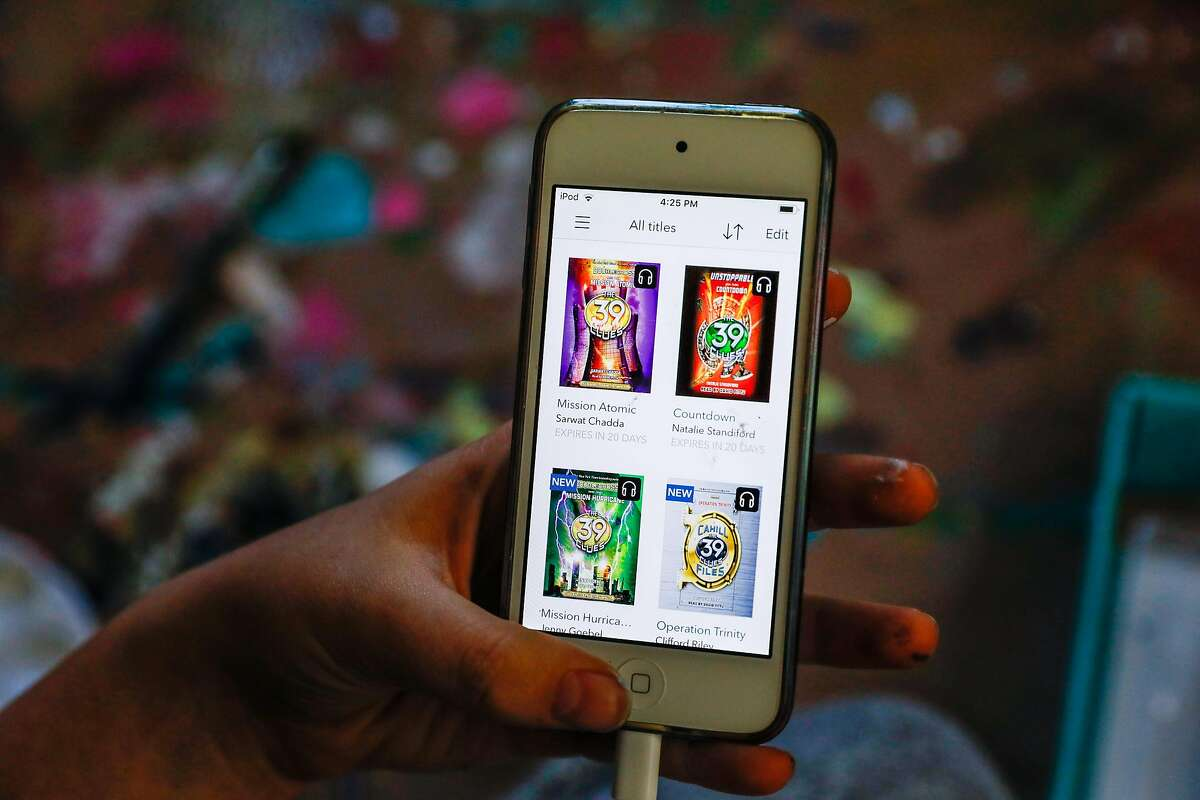 Rory Schroeder,11, explains how she downloads audio books onto her phone from the library app at her home during shelter-in-place orders on Thursday, April 23, 2020 in Berkeley, California.