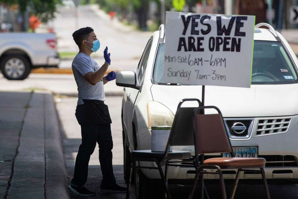 A worker at Blanco Cafe waves to a customer who pulled up for curbside pick up at the restaurant in San Antonio, Texas, on April 20, 2020. Mayor Ron Nirenberg issued a second addendum to start on April 20 to the Stay Home Work Safe requiring all people 10 years or older to wear a cloth face covering over their nose and mouth when in a public place.