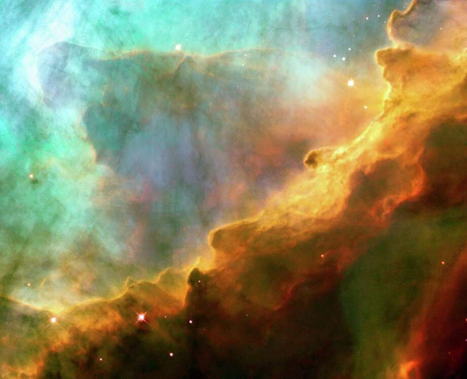 Resembling the fury of a raging sea, this image actually shows a bubbly ocean of glowing hydrogen gas and small amounts of other elements such as oxygen and sulfur. The photograph, taken, May 29-30, 1999 and released April 24, 2003 by NASA's Hubble Space Telescope, captures a small region within M17, a hotbed of star formation. M17, also known as the Omega or Swan Nebula, is located about 5,500 light-years away in the constellation Sagittarius. The image is being released to commemorate the thirteenth anniversary of Hubble's launch on April 24, 1990. The image, roughly 3 light-years across with the Wide Field Planetary Camera 2. The colors in the image represent various gases. Red represents sulfur; green, hydrogen; and blue, oxygen. Photo: NASA / AP / NASA HUBBLE