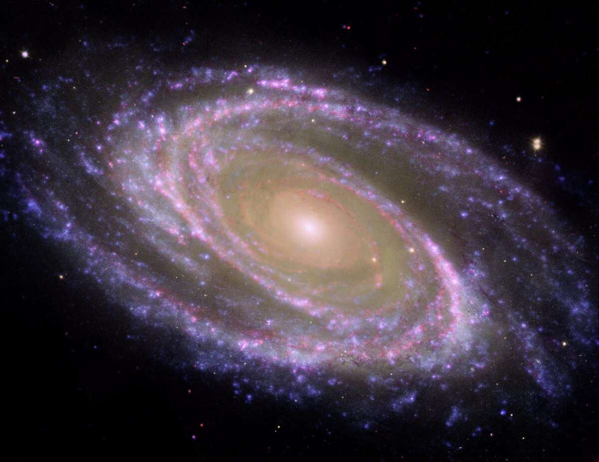 """This beautiful galaxy is tilted at an oblique angle on to our line of sight, giving a """"birds-eye view"""" of the spiral structure. The galaxy is similar to our Milky Way, but our favorable view provides a better picture of the typical architecture of spiral galaxies. M81 may be undergoing a surge of star formation along the spiral arms due to a close encounter it may have had with its nearby spiral galaxy NGC 3077 and a nearby starburst galaxy (M82) about 300 million years ago. M81 is one of the brightest galaxies that can be seen from the Earth. It is high in the northern sky in the circumpolar constellation Ursa Major, the Great Bear. At an apparent magnitude of 6.8 it is just at the limit of naked-eye visibility. The galaxy's angular size is about the same as that of the Full Moon. This image combines data from the Hubble Space Telescope, the Spitzer Space Telescope, and the Galaxy Evolution Explorer (GALEX) missions. The GALEX ultraviolet data were from the far-UV portion of the spectrum (135 to 175 nanometers). The Spitzer infrared data were taken with the IRAC 4 detector (8 microns). The Hubble data were taken at the blue portion of the spectrum."""