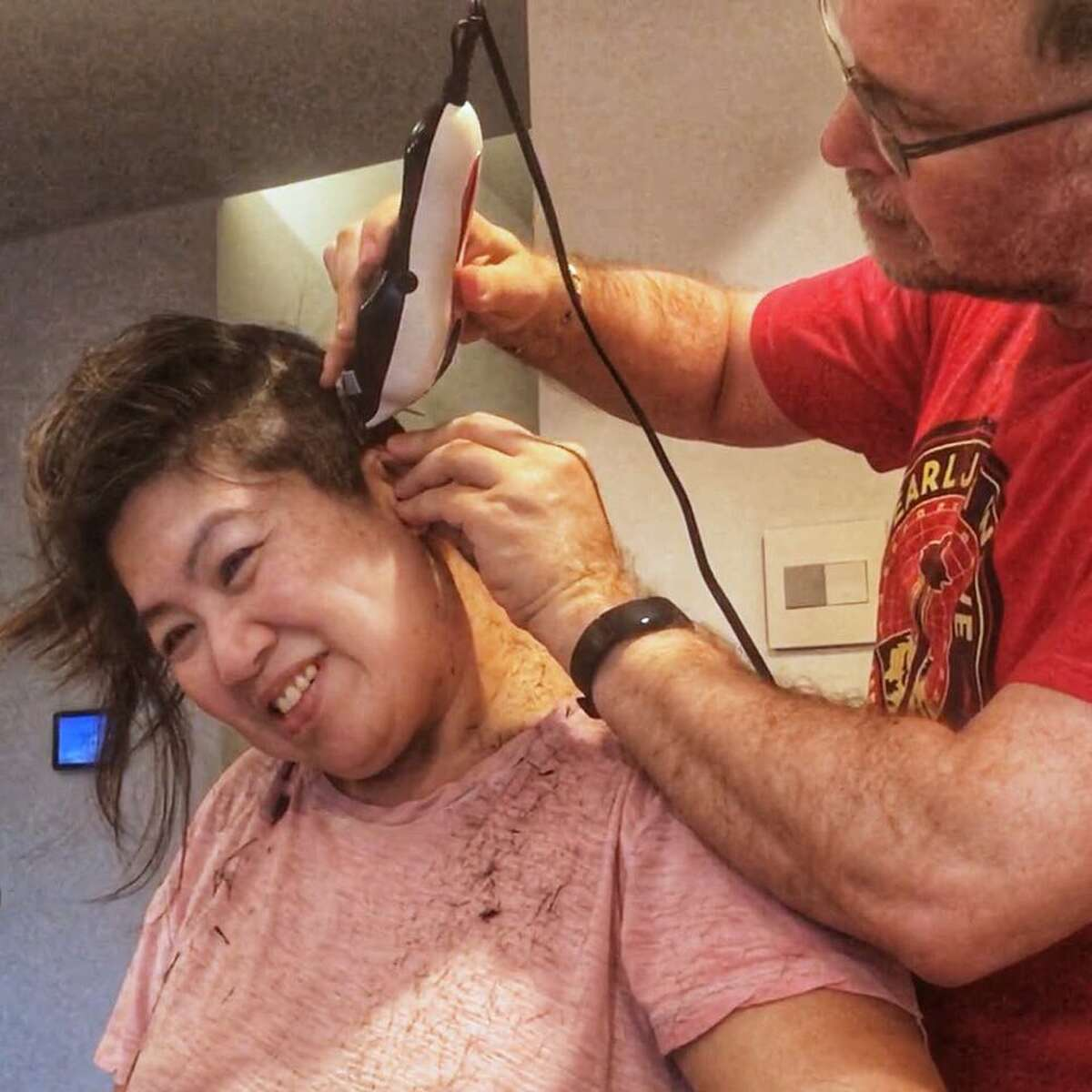 Eric Riddle cuts his wife's hair, Hsiao-Ching Chou. She is the author of