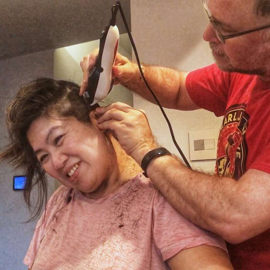 "Eric Riddle cuts his wife's hair, Hsiao-Ching Chou. She is the author of ""Chinese Soul Food,"" a well-known Seattle cooking teacher and author, and the former Seattle Post-Intelligencer food editor. Photo: Courtesy Eric Riddle"