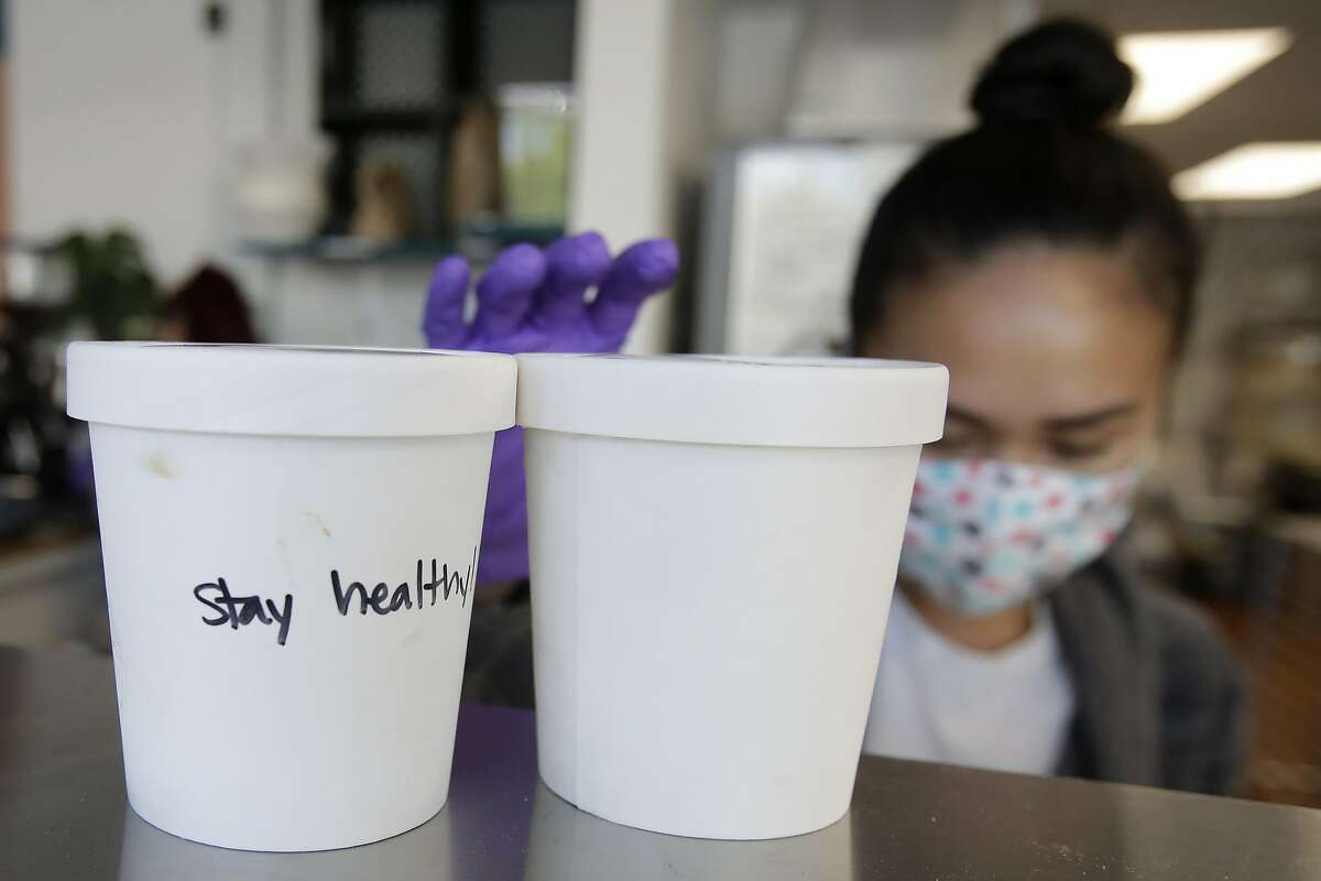 """A note that reads """"Stay healthy"""" is written on a container of ice cream in front of Churn Urban Creamery owner, Rica Sunga-Kwan, at the shop in San Francisco, Thursday, April 23, 2020. Churn, which had closed days before San Francisco's shelter in place orders due to coronavirus concerns, reopened on April 1, for online orders and curbside pickup, and created an online store to sell supplies such as flour, sugar, toilet paper and other items they had for their ice cream business to customers. (AP Photo/Jeff Chiu)"""