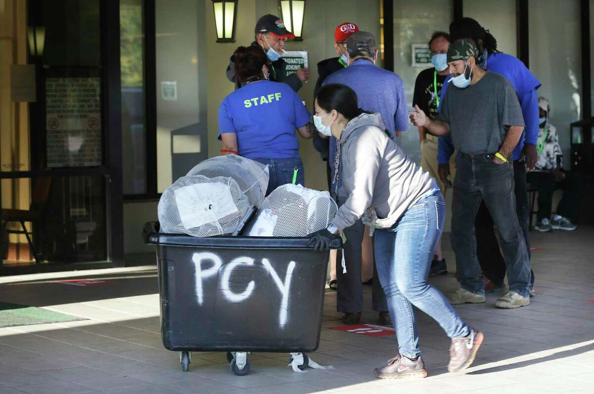 The city of San Antonio and Haven for Hope are using the Holiday Inn Hotel building located at 318 W. Cesar Chavez Blvd. to house some of the homeless. A worker pushes a cart labled PCY, for Prospects Courtyard, with bags of personal items. A reader praises the city's efforts to help the homeless, saying it demonstrates compassion in action.