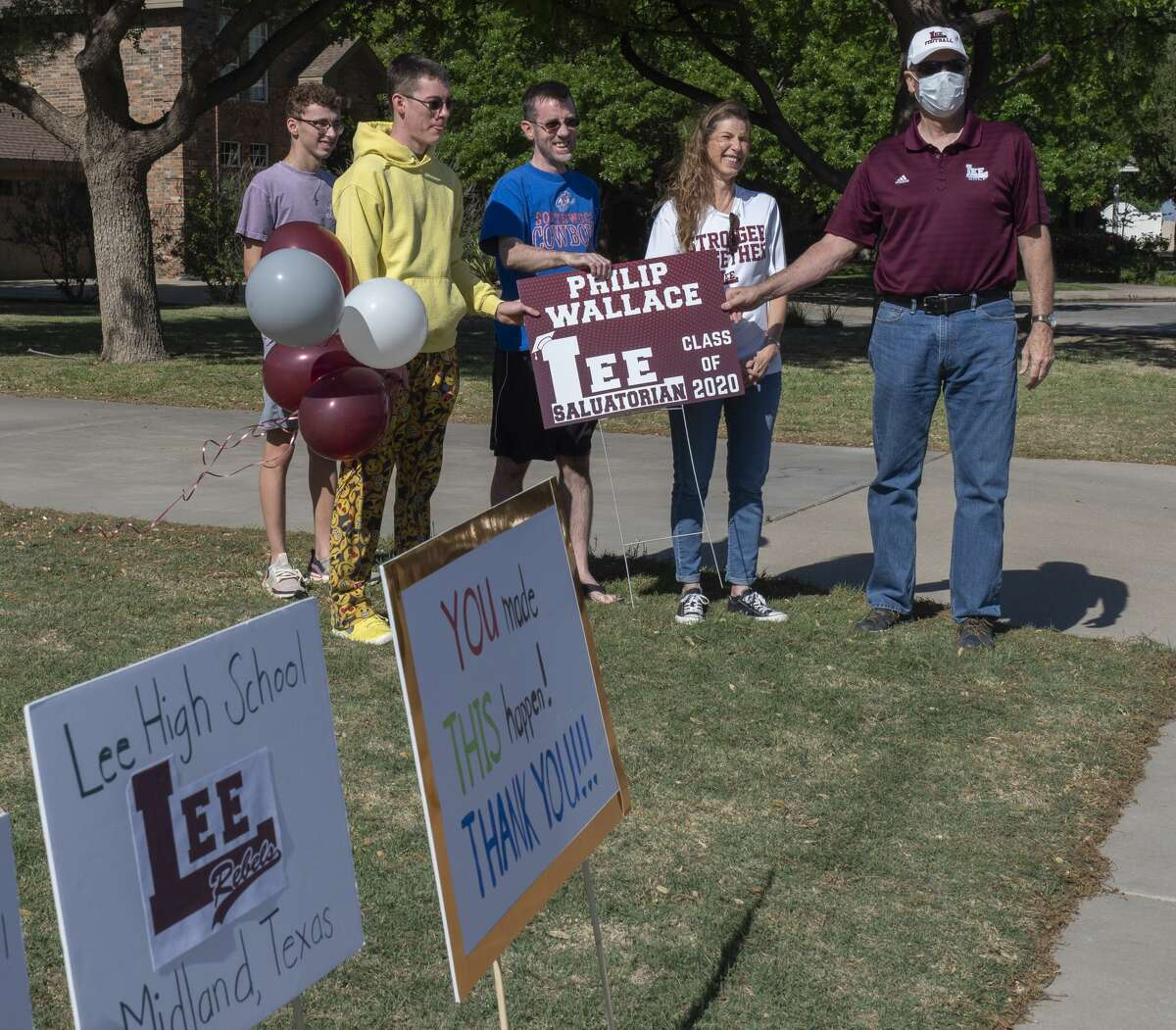 Lee High administrators and counselors caravan through town 04/24/2020 stopping to honor the top 10 seniors of 2020. Principal Stan VanHoozer presents PJ Wallace the #2, salutatorian, senior for LHS. Tim Fischer/Reporter-Telegram
