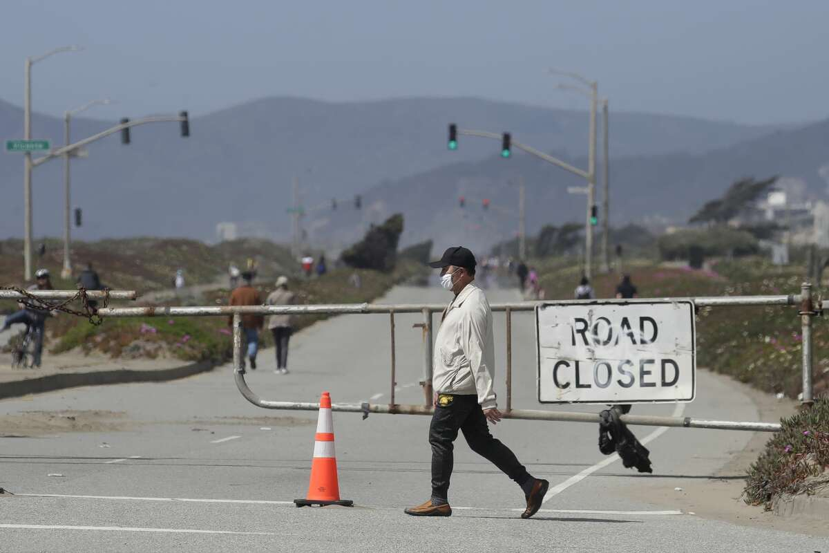 A man wearing a mask walks past a road closure sign next to Ocean Beach in San Francisco, Thursday, April 23, 2020.