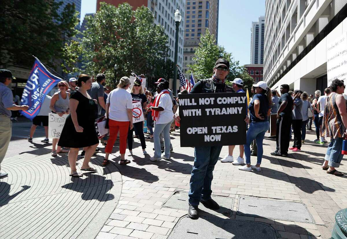 """A man holds a sign that reads """"Will Not Comply with Tyranny Open Texas Now"""" while Dr. Steven Hotze lead protesters to rally outside of 1001 Preston Street downtown, in Houston, Thursday, April 23, 2020. They were protesting against Harris Count Judge Lina Hidalgo's orders to wear masks starting Monday."""