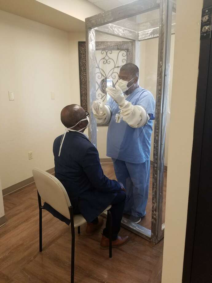 Dean of engineering George Nnanna displays how the plexiglass booth for coronavirus testing works with chief medical officer Dr. Rohith Saravanan at Odessa Regional Medical Center. Photo: Courtesy Photos