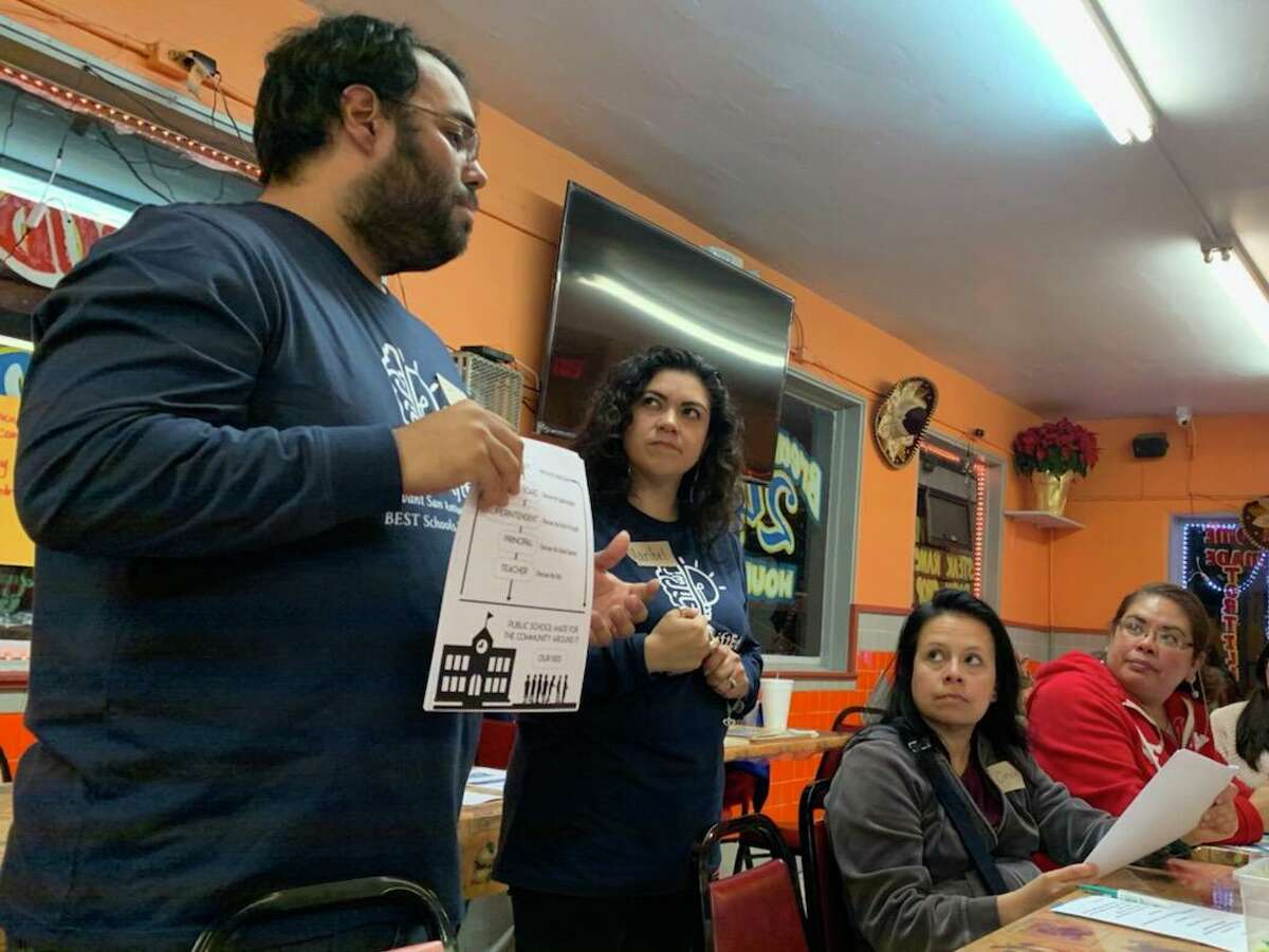 Joe Cantu (from left) and Maribel Gardea explain to parents how to research their schools' accountability ratings from the Texas Education Agency at a meeting at Rocky's Taco House last December.